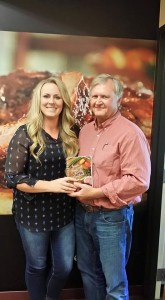 "Food blogger and farmer Cristen Clark presents a signed copy of a cookbook to ""Musings of a Pig Farmer"" blogger Larry Sailer"