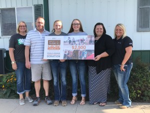 The Bell Family (from Left to Right Kerri, Lance, Sophie, & Elle) presenting a check to the local 4-H Scholarship Fund.